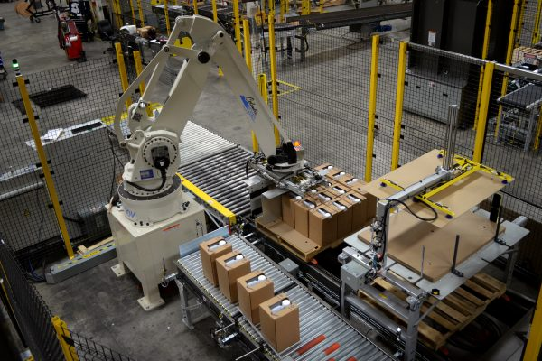The picture shows a white Columbia Okura palletizer placing small crates on a conveyor belt.