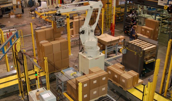 Industrial robot peforming palletizing of boxes from yellow conveyors.