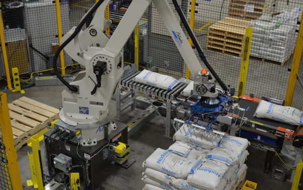 Industrial robot palletizing bags of product from a conveyor.