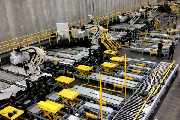 The image shows a huge room with machines and a conveyer belt