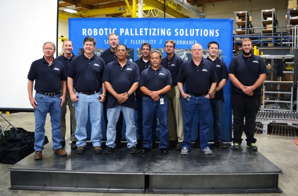 11 men wearing Columbia polos stand in front of the blue Robotic Palletizing Solutions banner. They look happy and proud.