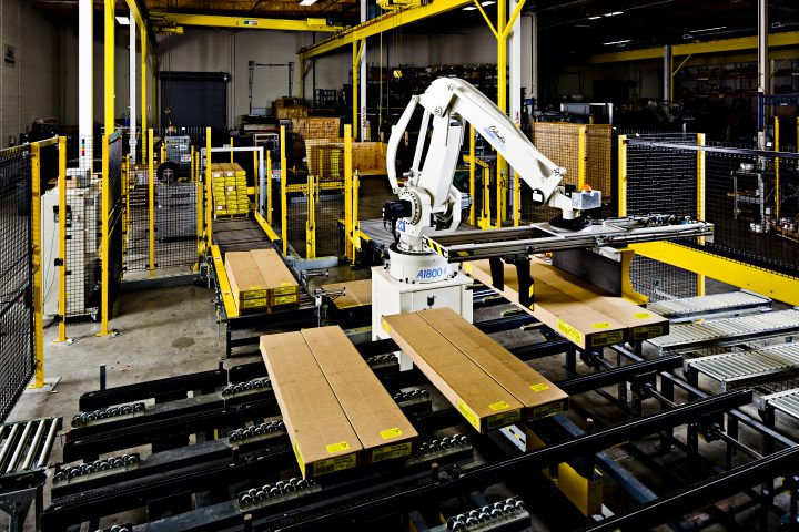 Columbia/Okura robotic palletizer moves lumber from a conveyor.