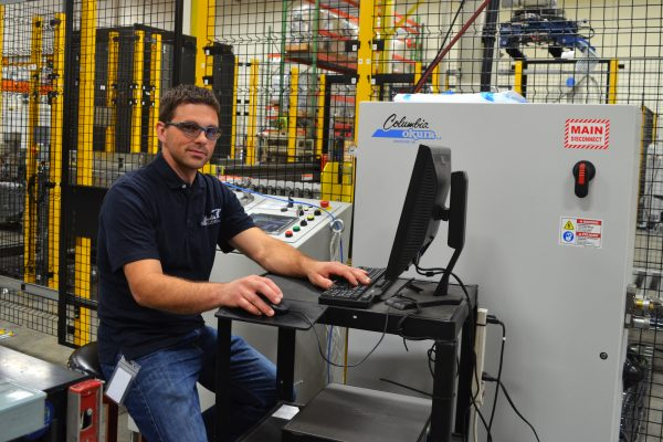 A man wearing glasses sits at a computer near a robotic palletizing system