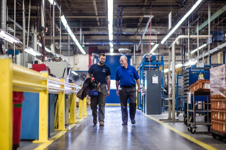 Two men walking in the middle of the spacious room in an industrial building. There are machines on the both sides of them.