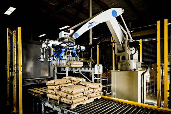 A Columbia Okura robotic arm is placing bags on the conveyor belt